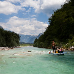 family canoeing on soča with julian alps at the back