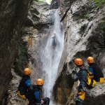 friends sliding down the last waterfall in sušec canyon