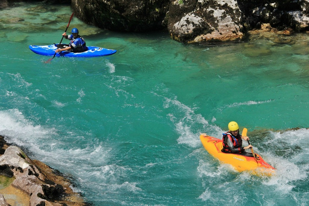 two kayakers playing on the rapids of the soča river