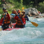 adventurous friends canoeing on soča river in slovenia