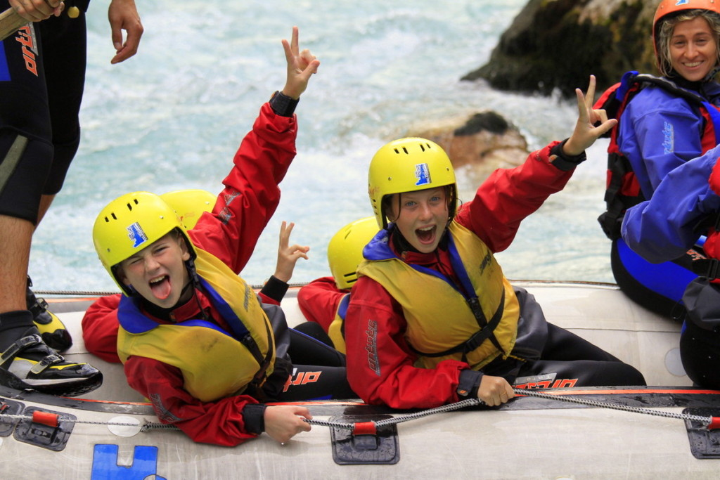 girls enjoying family adventure rafting with parents