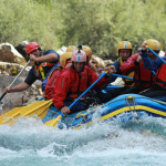 group of friends rafting on the rapids