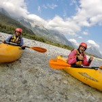 couple on a kayak course with julian alps at the back