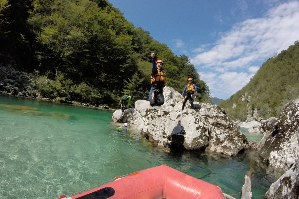 friends on canoe trip jumpin off the rocks to soča river