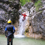 sliding down a small waterfall fratarca canyoning in soča valley