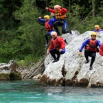 group of friends jumping from the rock to the soča river