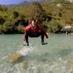 man jumpin on soča river in neoprene suits
