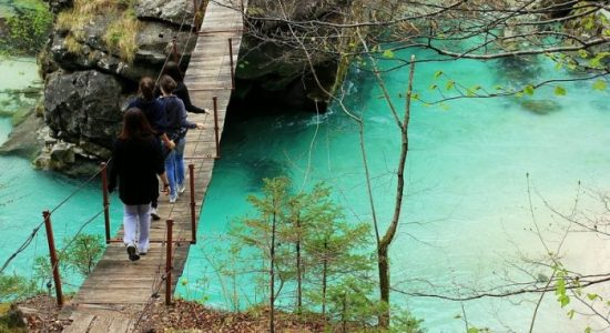 friends walking on the hanging bridge over the soča river