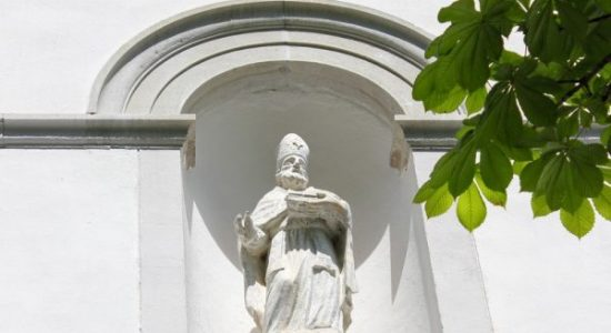 stone statue of st ulrich at the entrance of parrish church of bovec
