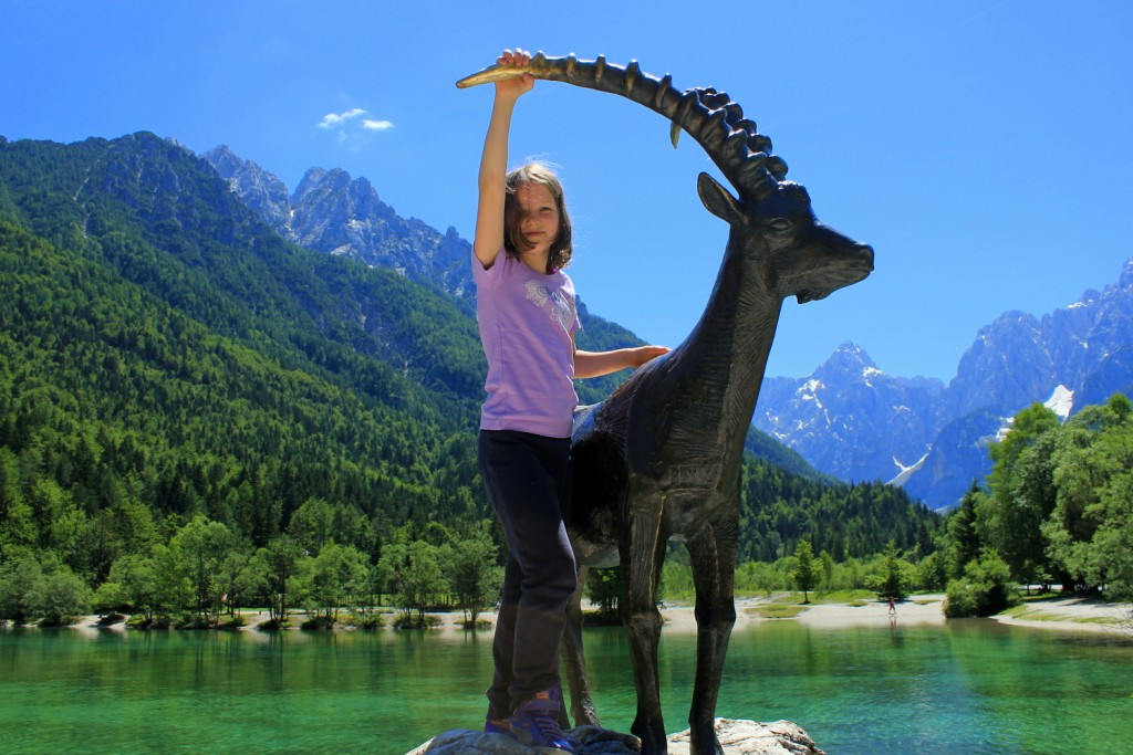 girl at jasna lake in kranjska gora by the statue of zlatorog